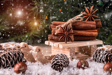 Christmas card with wooden sled with heap of cinnamon
