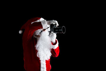 Santa claus taking picture with his camera isolated on black