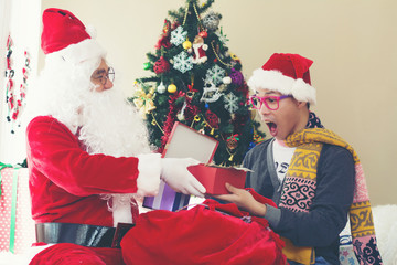 Santa Claus and the young boy with gift boxes. Miracles on Christmas.
