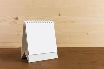 White blank paper desk spiral calendar on wood background..
