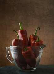 Red Anaheim peppers in glass cup on slate with room for copy