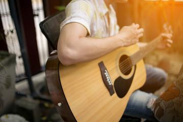 asia Guy plays guitar in the backyard.