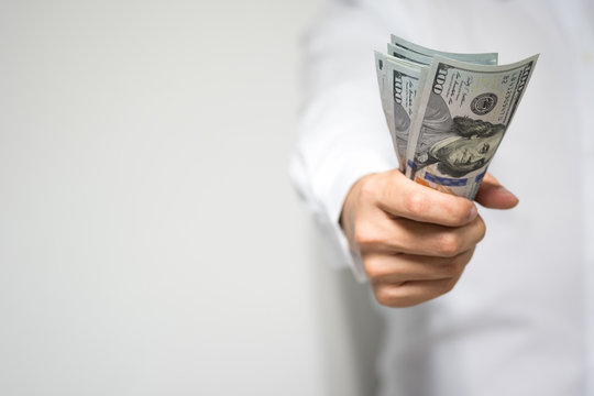 Very happy businessman hand holding and grabbing US dollar (USD) money bills in hand and passing to client in concept of investment, success and profitable business.