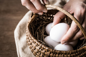 Farmer taking a white egg from the basket. Rustic kitchen. Farm food concept.