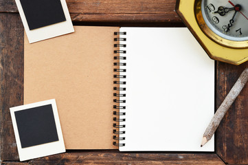 Blank notebook, photo frame, pencil and clock on wooden background