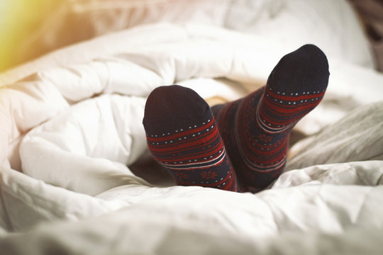 Legs of a girl in socks against the background of a bed. Added effect