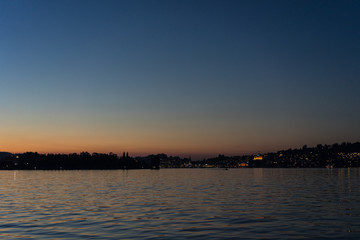 sunset on lake lucerne viewed from boat with city background