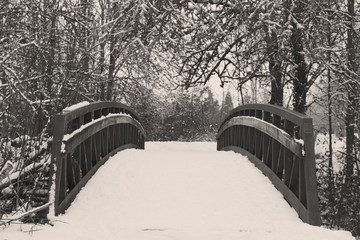 Black and White Vintage Style Image of Snow Covered Wooden Bridge in Wooded Area, Daytime
