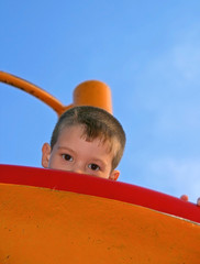 colorful and contrasting image with a little boy who hiding while playing on playground. Funny pictures.