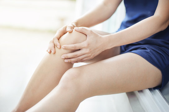 woman runner suffering from knee pain sit on the floor