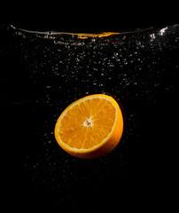 orange in water on a black background