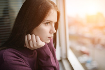 Sad woman looking through the window at sunset. Wall mural