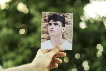 Mano de joven sujetando una foto con el retrato de un hombre joven con media luna dibujada en la cara sobre fondo frondoso.