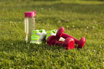 dumbbells and sneakers on the grass. sports equipment, fitness and sports.
