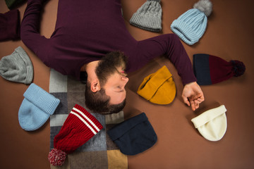 man lying between scattered hats
