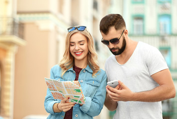 Young tourists with map on the street