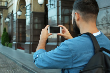 Young male tourist taking photo on the street