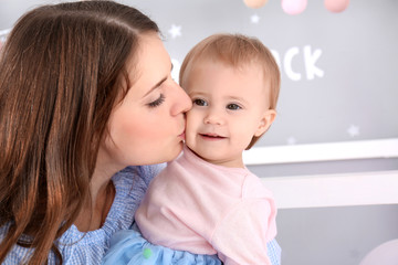 Young mother kissing cute baby at home