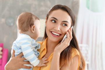 Young mother holding baby while talking on phone at home