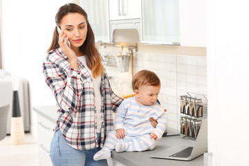 Young woman with baby working in home office