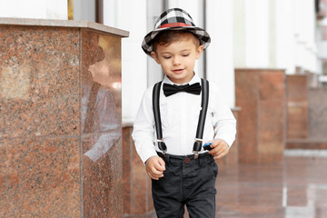 Adorable little boy standing near building outdoors