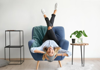 Attractive hipster girl in armchair at home