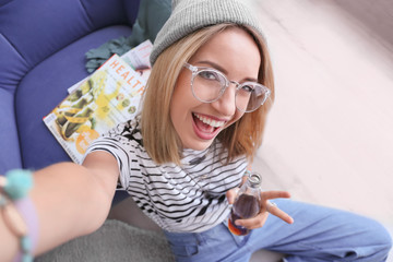 Attractive hipster girl taking selfie at home