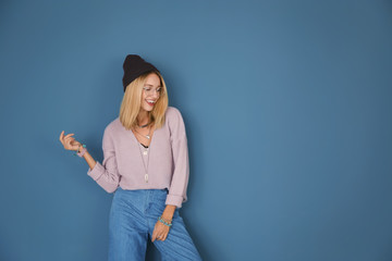 Attractive hipster girl on color background