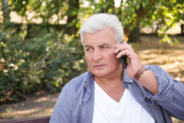 Handsome mature man using cell phone in park