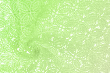 Image texture background, decorative lace with pattern.  green vintage lace background. Green lace on white spandex background, macro view. Ornamental round lace