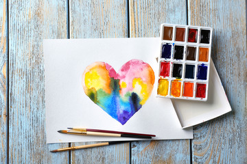 Painting of rainbow heart on wooden background