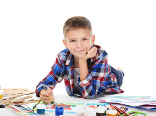 Cute little boy painting against white background