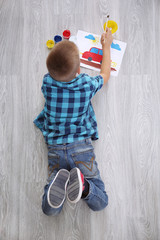Cute boy painting picture on sheet of paper, indoors