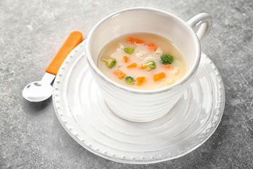 Mug with creamy soup for baby on table