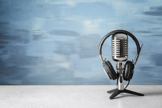 Retro microphone and headphones on table against blue wall