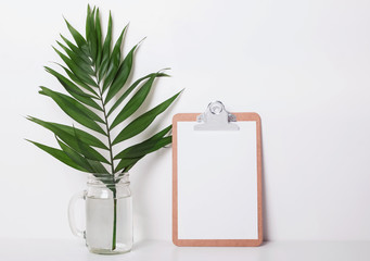 Clipboard with empty paper and tropic leaf in the jar.