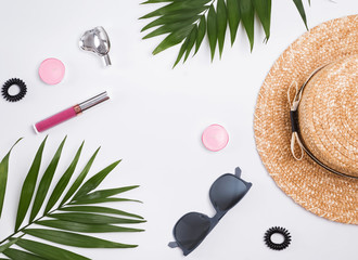 Straw hat, sunglasses and palm leaves on the white background.