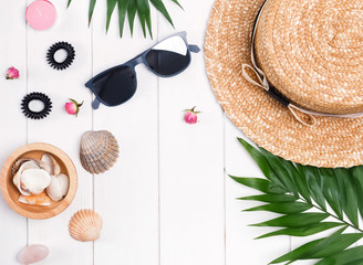 Flat lay with straw hat, sunglasses, palm leaves and feminine accessories