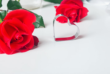 Red roses and heart shape metal mold on the white backgorund