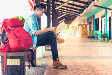 Tourist young man holding a map searching direction on location map. Happy enjoying adventure travel alone by train. Tourist searching location concept