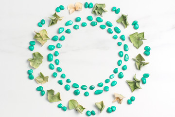Beautiful frame of dried flowers of hydrangeas and pebbles of turquoise color. Marble background. View from above, flat lay
