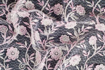 Texture, background, pattern. Pink lace decorated with flowers on a black background. Lace decorated with a pattern and decorative rose on a black background.