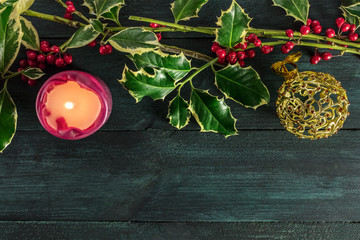 Christmas template with holly branches, candle, and copy space