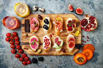 Appetizers table with italian antipasti snacks and wine. Brushetta or authentic traditional spanish tapas set on wooden rustic board over grey concrete background. Top view, flat lay
