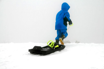Kid dressed in blue winter sport suit pulling sledge uphill