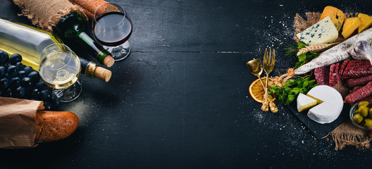 A bottle of wine, cheeses and traditional sausages on a wooden background. Brie cheese, blue...