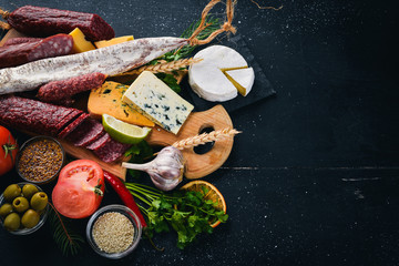 Assortment of cheeses and traditional sausages on a wooden background. Brie cheese, blue cheese, gorgonzola, fuete, salami. Free space for text. Top view.