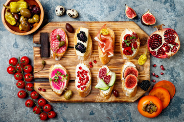Appetizers table with italian antipasti snacks. Brushetta or authentic traditional spanish tapas set on wooden rustic board over grey concrete background. Top view, flat lay