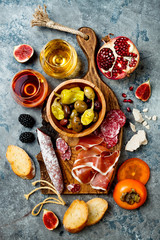 Appetizers table with italian antipasti snacks and wine in glasses. Charcuterie board over grey concrete background. Top view, flat lay