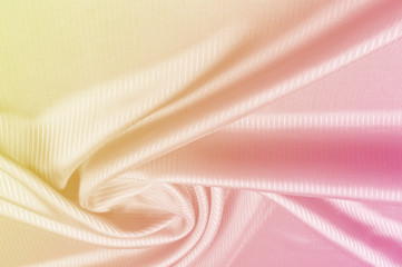 Background pattern, texture. Silk fabric yellow pink pastel tones. Silk background in pink and yellow colors.
